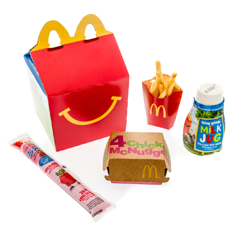 Winneconne, WI - 7 August 2018: A Chicken McNuggets happy meal with white milk and yogurt on an isolated background