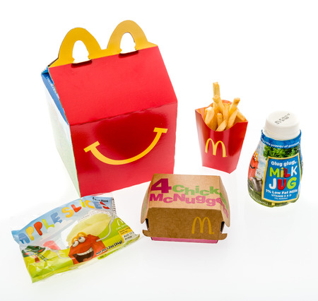 Winneconne, WI - 7 August 2018: A Chicken McNuggets happy meal with white milk and apple slices on an isolated background Stock Photo - 109598033