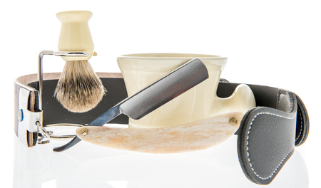A straight razor with a leather strap for sharpening and brush and cup to create foam on an isolated background