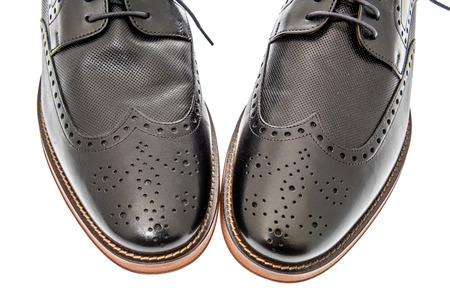 A close-up shot of a pair of mens black wingtip dress shoes on an isolated background