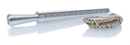 A ring sizer and rings for measuring fingers for ring size on an isolated background.