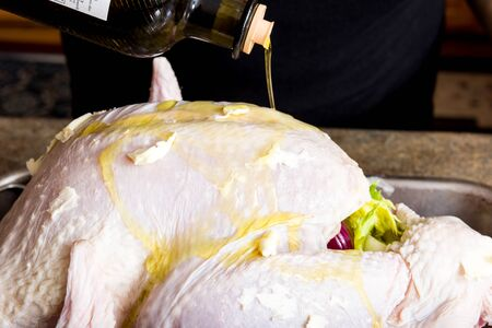 A turkey with oil being added for flavor on a pan for preparation 版權商用圖片 - 139828183