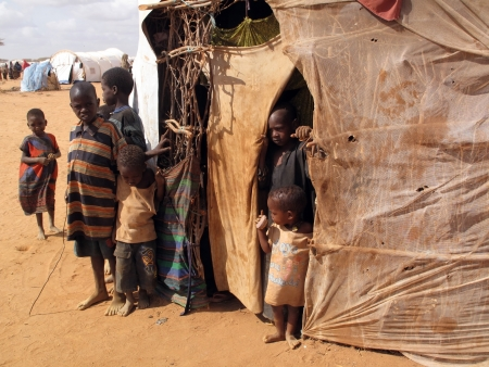 Dadaab, Somalia-August 15,2011: Woman & children live in the Dadaab refugee camp where thousands of Somalis wait for help because of hunger  in Dadaab, Somalia.                                                Stock Photo - 16704671