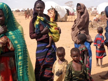 Woman and children live in the Dadaab refugee camp where thousands of Somalis wait for help because of hunger  in Dadaab, Somalia.                              Stock Photo - 16704660