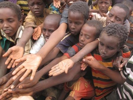 gente pobre: Los niños extienden sus manos en el campamento de refugiados de Dadaab, donde miles de espera para ayudar a Somalia a causa del hambre en Dadaab, Somalia.