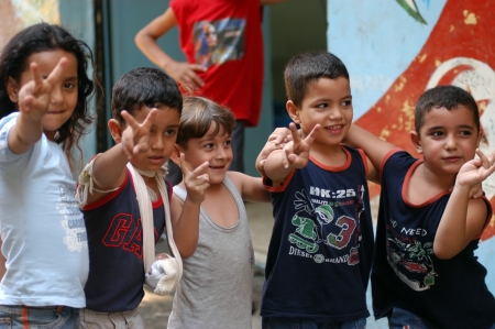 war refugee: BEIRUT, LEBANON-AUGUST 2:Unidentified Palestinian children make victory sign in Shatila refugee camp on August 2, 2006 in Beirut,Lebanon