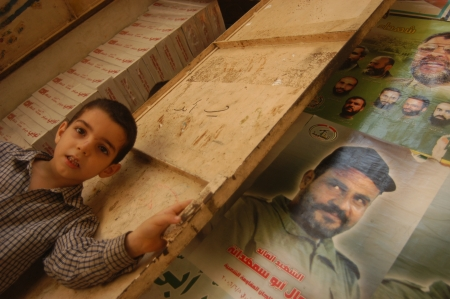 BEIRUT, LEBANON-AUGUST 2:Unidentified child goes in a room in Shatila refugee camp on August 2, 2006 in Beirut,Lebanon. On the wall there are posters of dead Hamas leaders. Stock Photo - 16817418