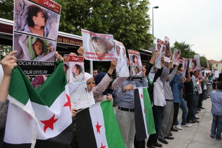 al assad: Istanbul, Turkey-May 29, 2012: A group of unidentified people stage a demonstration in front of the Fatih Mosque, protesting Syrian authorities violent crackdown in Homs, on May 29, 2012 in Istanbul,Turkey