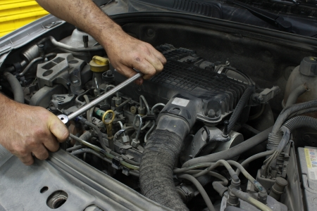 auto mechanic: Man holding a spanner over a car engine