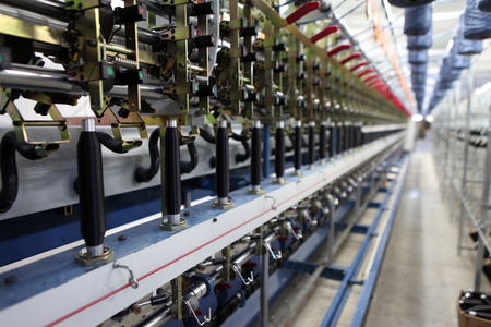 Textile fabric manufacturing machines in work. Textile industry.