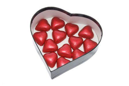 Chocolates on Heart-shaped Gift Box on White Background photo