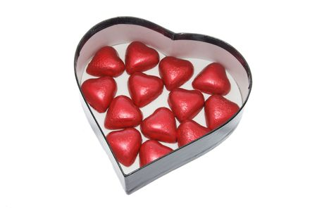Chocolates on Heart-shaped Gift Box on White Background photo