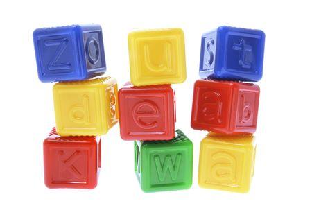 Stacks of Plastic Alphabet Cubes on White Background photo