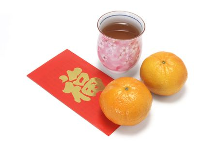 red packet: Cup of Chinese Tea with Mandarins on Red Packet on White Background Stock Photo