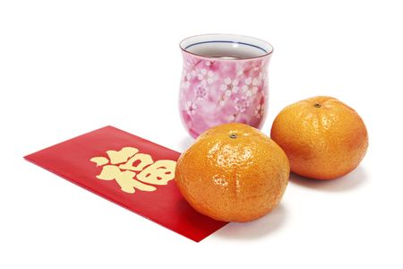Cup of Chinese Tea with Mandarins on Red Packet on White Background photo