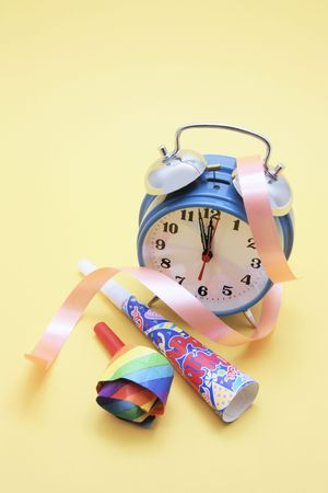 party favors: Party Favors and Alarm Clock on Yellow Background