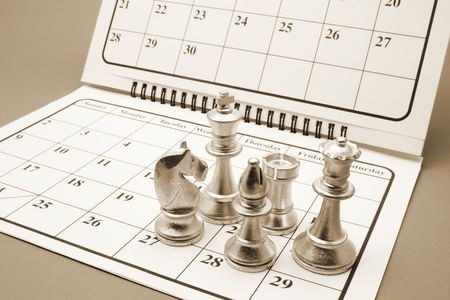 manoeuvre: Chess Pieces on Calendar in Warm Tone
