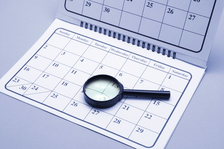 weeks: Magnifying Glass on Calendar in Blue Tone