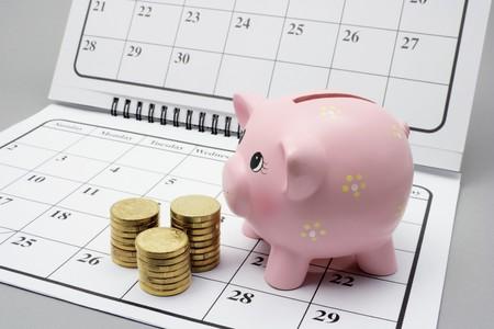 meses del a�o: Piggy Bank y monedas en el Calendario con fondo gris Foto de archivo