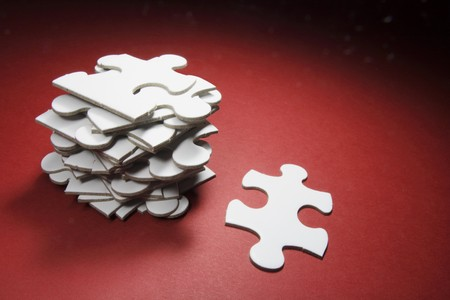 assembling: Jigsaw Puzzle Pieces on Red Background