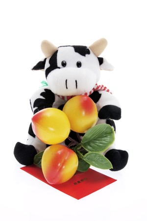 Soft Toy Cow and Tangerine Ornament on White Background photo