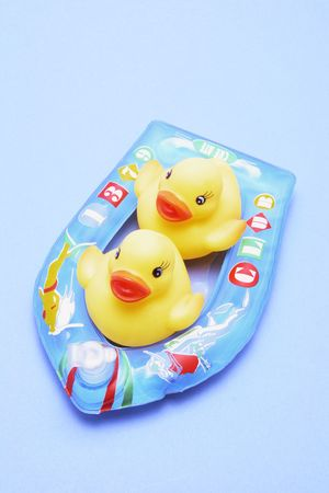 floater: Rubber Ducks on Inflatable Boat on Blue Background