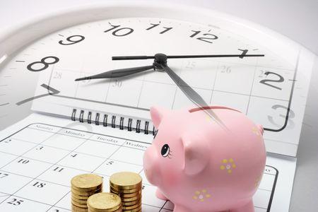 puntualidad: Piggy Bank y monedas en el Calendario con fondo gris Foto de archivo