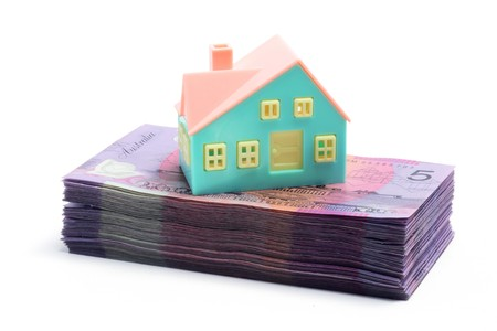 Stack of Notes with Miniature House on White Background photo