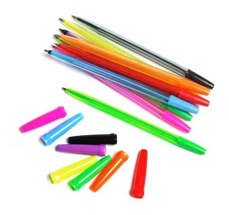 ball pens stationery: Plumas de bol�grafo y gorras sobre fondo blanco