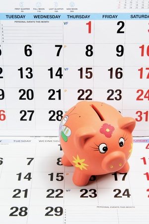 Close Up of Piggy Bank on Calendar Pages photo