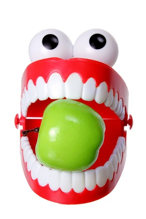 Chattering Teeth with Apple on White Background photo