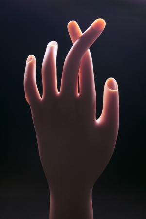 crossed fingers: Crossed Fingers on Black Background Stock Photo