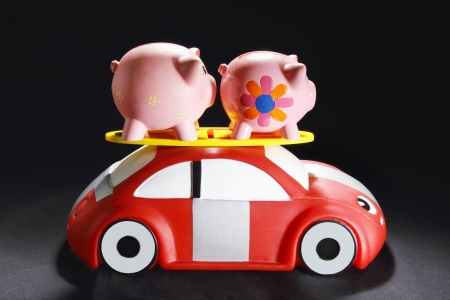 Piggybanks on Toy Car with Black Background photo