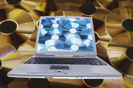 Composite of Laptop and Compact Discs Stock Photo