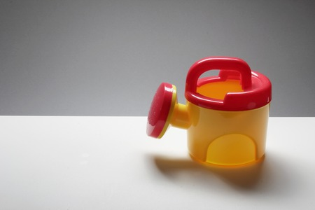 water conservation: Toy Watering Can Stock Photo