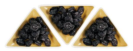 ciruela pasa: Los platos de la pasa con el fondo blanco Foto de archivo