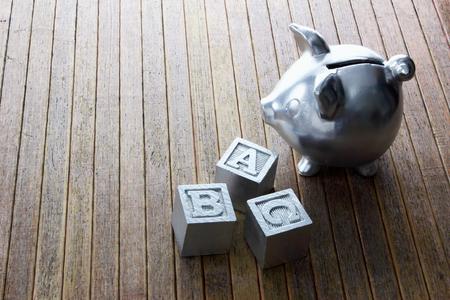 piggybank: Piggybank and Alphabet Cubes on Wooden Background