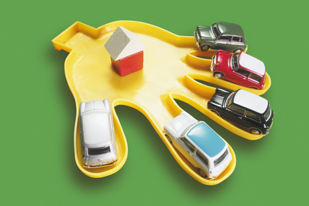 motorcars: Plastic Hand with Toy Cars on Green Background
