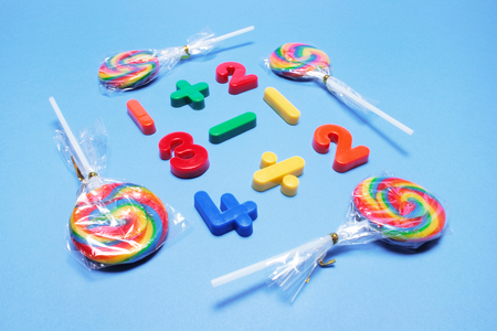 Lollipops with Plastic Numbers on Blue Background
