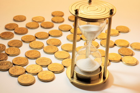 Hourglass and Coins on Warm Background Stock Photo