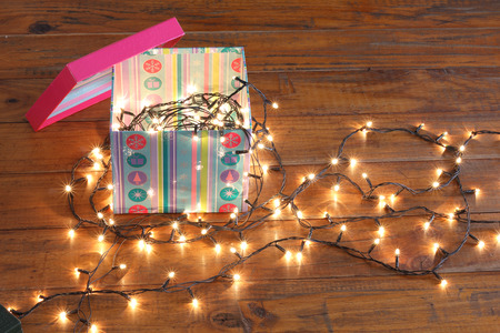 Gift Box and Fairy Lights on Wooden Background