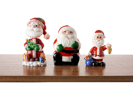 Santa Clause Figurines on Wooden Shelf
