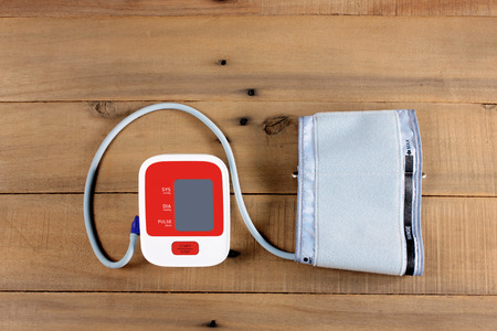 Blood Pressure Monitor on Wooden Background
