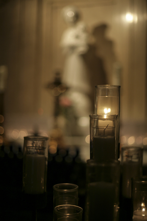lit candle in dark christian church with statue in background