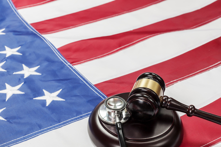 criminal case: Wooden judge gavel and soundboard laying over US flag Stock Photo
