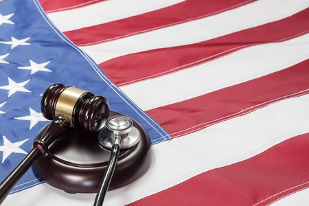soundboard: Wooden judge gavel and soundboard laying over US flag Stock Photo