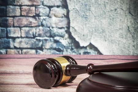 adjournment: gavel on a vintage wall background