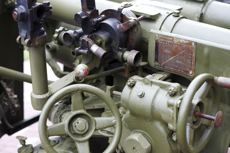 prompting: Aiming mechanism on the gun , retro military equipment , up close