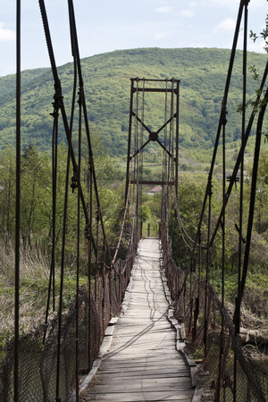 hinged: a hinged bridge over mountain river Stock Photo