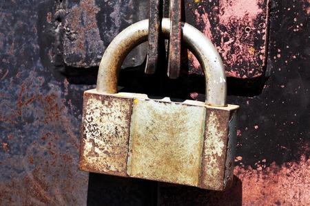 iron curtains: a Vintage rusty padlock metal gates